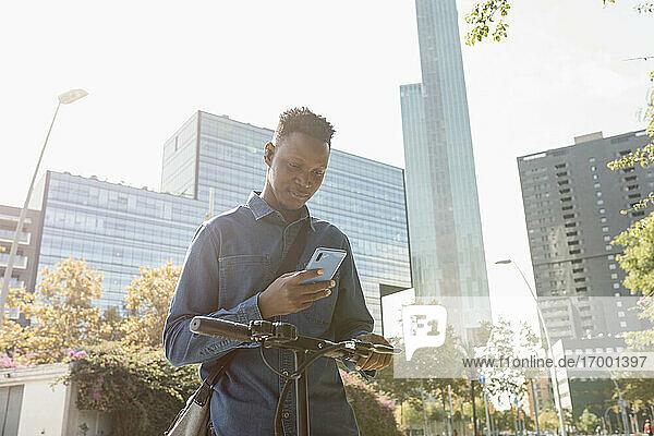 Männlicher Unternehmer  der ein Smartphone mit einem Elektroroller vor einem Gebäude in der Stadt benutzt Männlicher Unternehmer, der ein Smartphone mit einem Elektroroller vor einem Gebäude in der Stadt benutzt