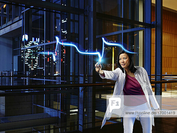 Mature female cardiologist light painting heart attack pulse in laboratory at hospital