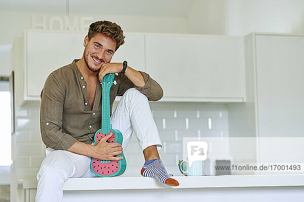 Smiling man sitting with ukulele over kitchen counter at home