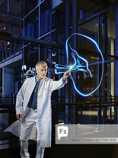 Männlicher Arzt  der seine Milz im Labor des Krankenhauses anmalt Männlicher Arzt, der seine Milz im Labor des Krankenhauses anmalt
