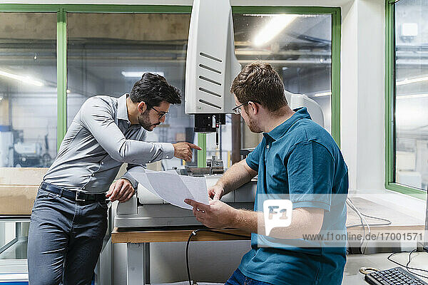 Businessman and male colleague examining surveyor machine at factory