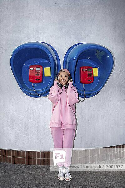 Lächelnde junge Frau mit rosa Haaren und rosa Kapuzenshirt vor einer Telefonzelle stehend Lächelnde junge Frau mit rosa Haaren und rosa Kapuzenshirt vor einer Telefonzelle stehend