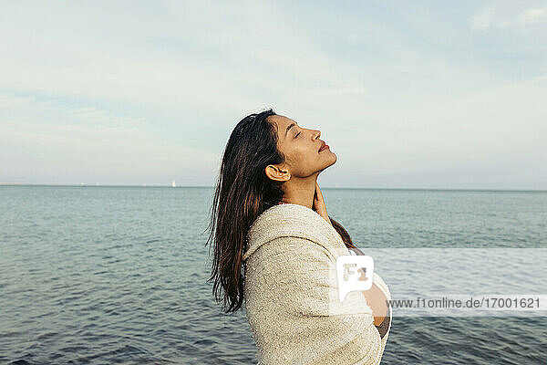 Junge Frau mit geschlossenen Augen steht gegen den Himmel am Strand Junge Frau mit geschlossenen Augen steht gegen den Himmel am Strand