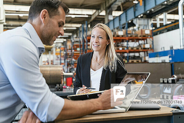 Smiling female colleague looking at male entrepreneur while standing in factory