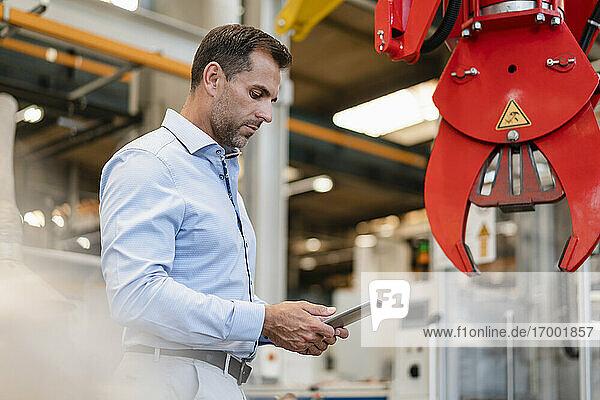 Male entrepreneur using digital tablet while standing in front of claw machinery at industry
