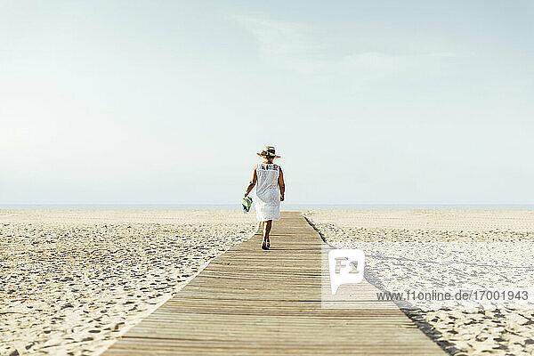 Senior woman walking on boardwalk on the beach  El Roc de Sant Gaieta  Spain