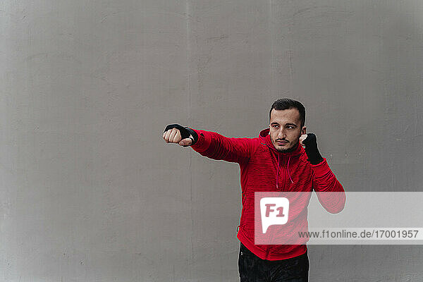 Sportsman boxing while standing against wall