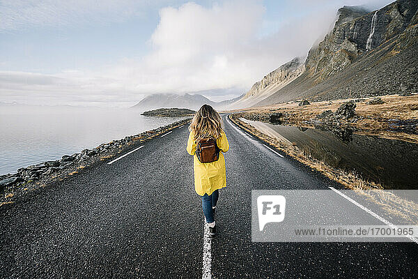 Iceland  back view of woman with backpack walking on median strip of country road