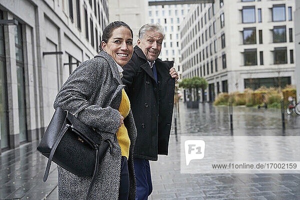 Smiling business couple looking away while standing on footpath