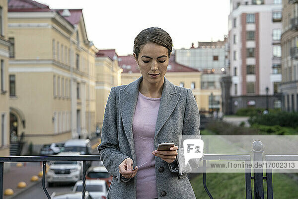 Female entrepreneur holding credit card while making payment through smart phone in city