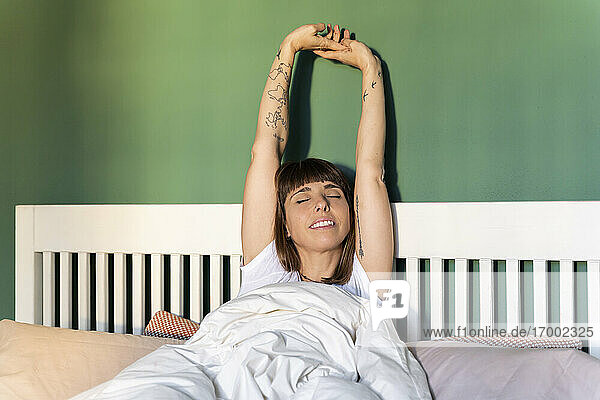 Mid adult woman stretching arms while waking up on bed at home