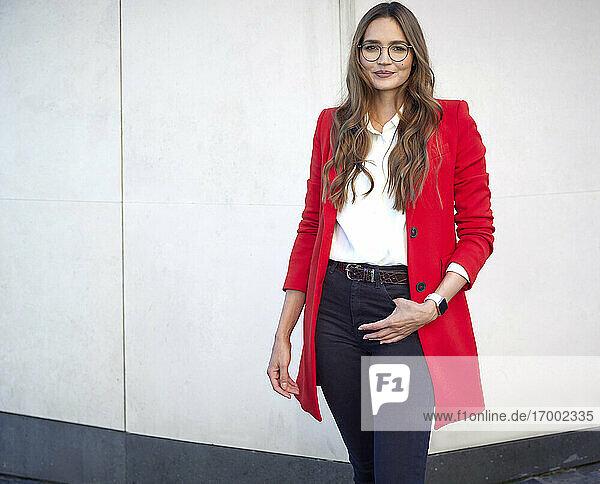 Confident businesswoman wearing blazer standing against wall