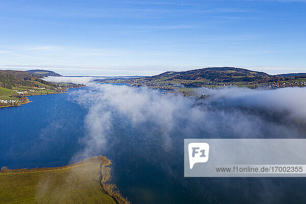 Drone view of fog floating over Irrsee lake