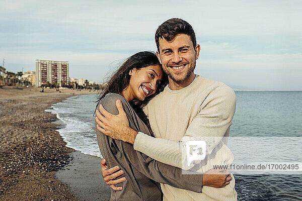 Lächelnde Freundin und Freund umarmen einander gegen den Himmel am Strand Lächelnde Freundin und Freund umarmen einander gegen den Himmel am Strand