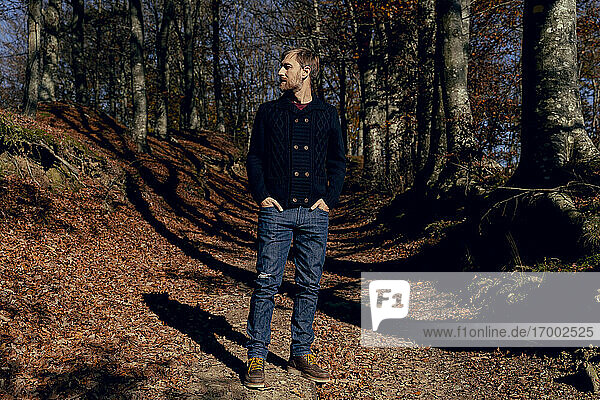 Man looking away while standing with hands in pockets on forest path