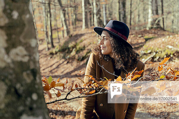 Mature woman smiling while looking around in forest
