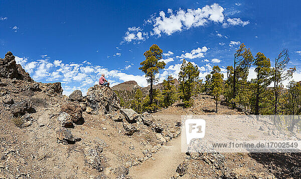 Man sitting on rock while hiking in Teide National Park  Tenerife  Canary Islands  Spain