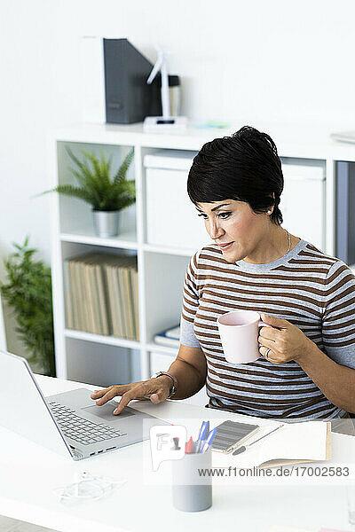 Porträt einer Geschäftsfrau mit Laptop am Bürotisch