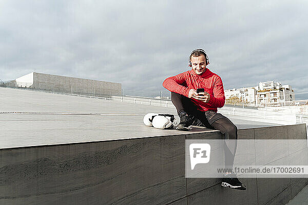 Sportsman with headphones using mobile phone sitting outdoors