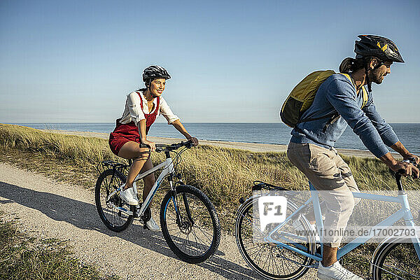 Young woman smiling while riding bicycle with man on footpath against sea