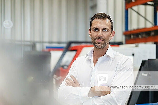 Smiling confident businessman with arms crossed at factory