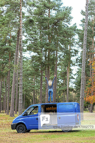 Mid adult woman with hands raised on top of motor home at Cannock Chase