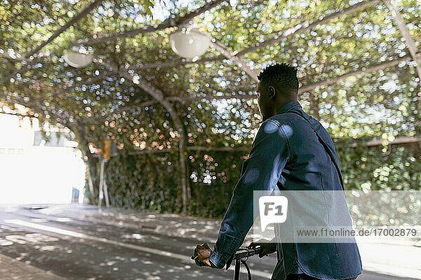 Männlicher Pendler  der mit einem Elektroroller durch einen Torbogen auf der Straße fährt Männlicher Pendler, der mit einem Elektroroller durch einen Torbogen auf der Straße fährt