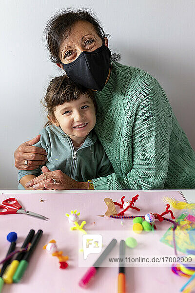 Grandmother embracing smiling granddaughter by table at home during pandemic