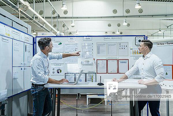 Geschäftsleute mit Laptop bei einer Besprechung am Schreibtisch in der Industrie