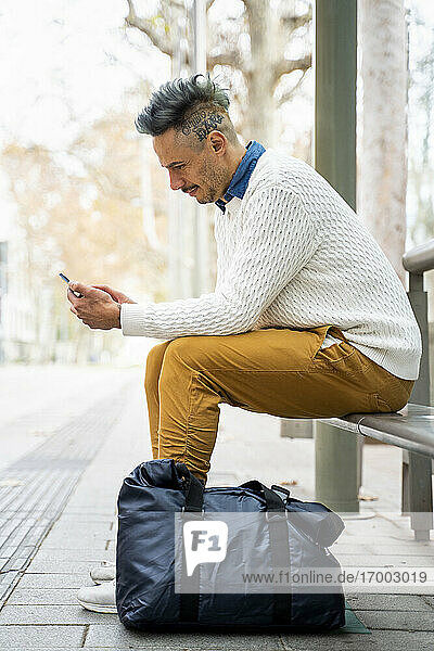 Male entrepreneur using smart phone while sitting at bus stop