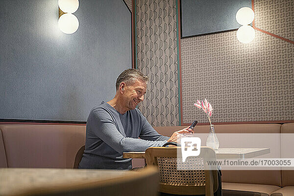 Businessman using mobile phone while sitting at modern cafe