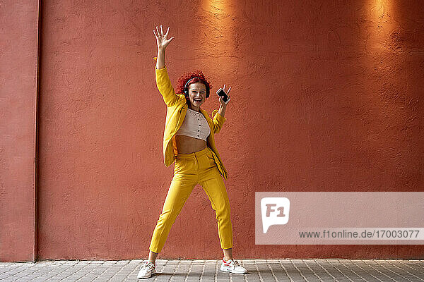 Young woman in yellow suit wearing headphones  dancing to music from her smartphone