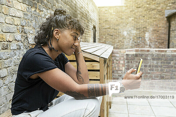 Smiling woman using mobile phone while sitting by wall at back yard