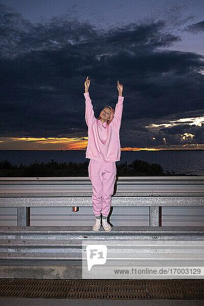 Junge Frau mit rosa Haaren  die ein rosa Trainingsanzug-Shirt trägt  steht in der Abenddämmerung auf einer Straßenschranke Junge Frau mit rosa Haaren, die ein rosa Trainingsanzug-Shirt trägt, steht in der Abenddämmerung auf einer Straßenschranke