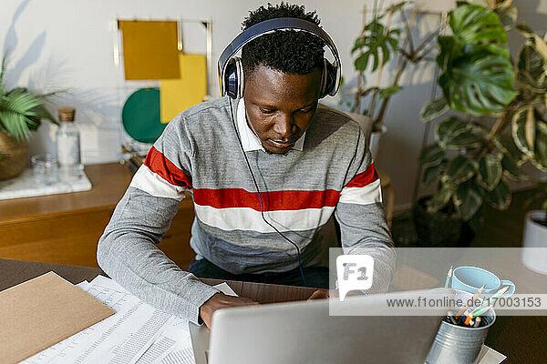 Afrikanischer Geschäftsmann mit Kopfhörern bei einem Videogespräch am Laptop zu Hause Afrikanischer Geschäftsmann mit Kopfhörern bei einem Videogespräch am Laptop zu Hause