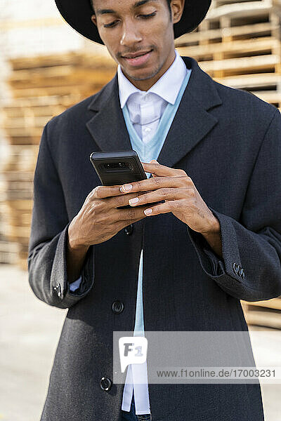 Fashionable young man using mobile phone