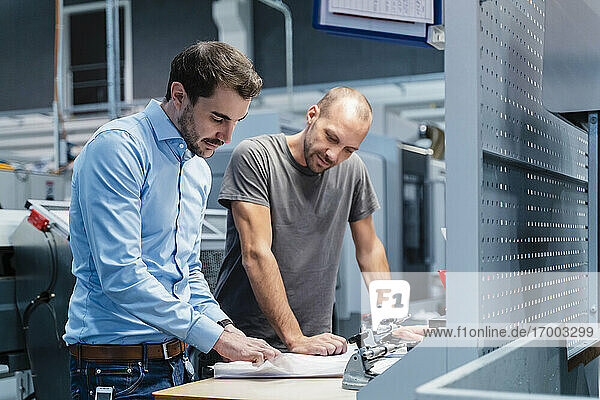 Male engineers analyzing plan while standing by table at industry