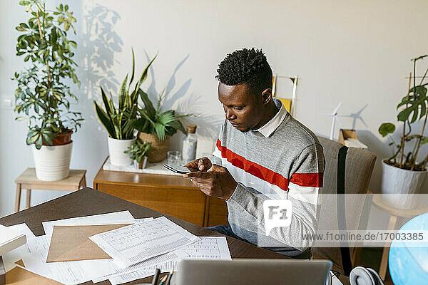 Männlicher Finanzberater fotografiert Kontodokument auf dem Schreibtisch im Büro zu Hause Männlicher Finanzberater fotografiert Kontodokument auf dem Schreibtisch im Büro zu Hause
