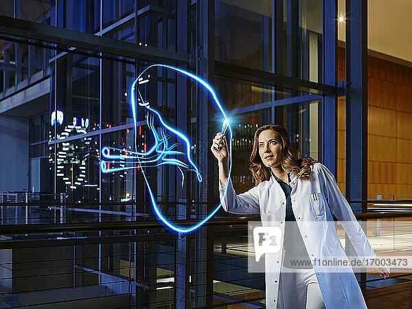 Female doctor light painting spleen in laboratory at hospital