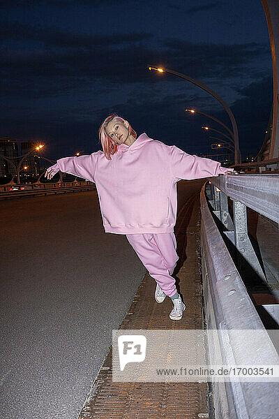 Junge Frau mit rosa Haaren und rosa Trainingsanzug steht nachts an einer Straßenschranke Junge Frau mit rosa Haaren und rosa Trainingsanzug steht nachts an einer Straßenschranke