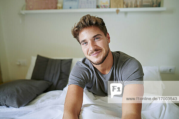 Young man smiling while sitting on bed in bedroom
