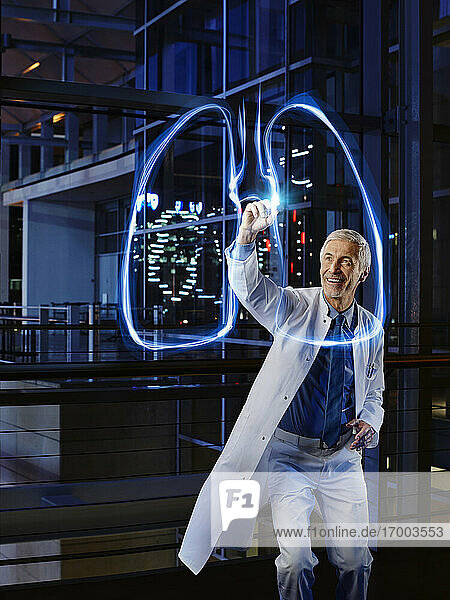 Smiling male pulmonologist light painting lung in laboratory at hospital