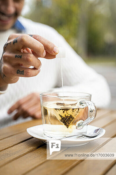 Man's hand dipping teabag in cup at cafe