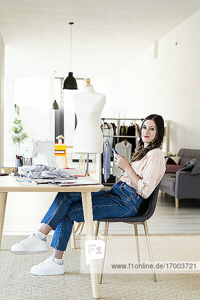 Smiling female designer holding smart phone while sitting on chair at studio
