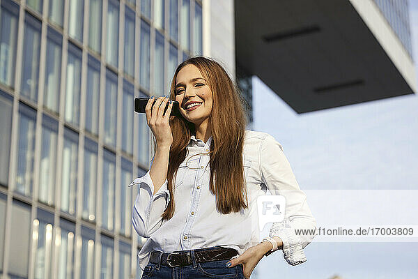 Smiling businesswoman talking on mobile phone while standing outdoors