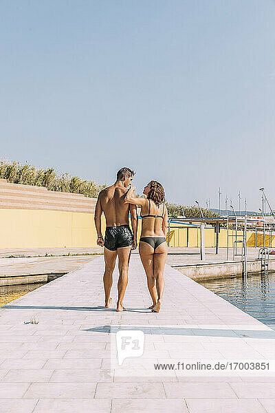 Young couple walking on a pier at the sea