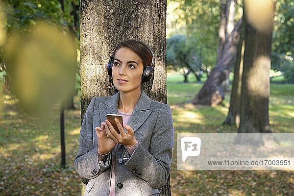 Nachdenkliche Geschäftsfrau hört Musik und hält ihr Smartphone im Herbst im Park Nachdenkliche Geschäftsfrau hört Musik und hält ihr Smartphone im Herbst im Park