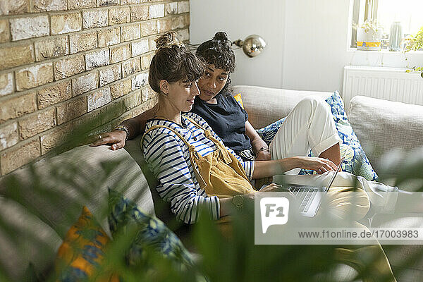 Girlfriend looking at woman using laptop while sitting on sofa at home
