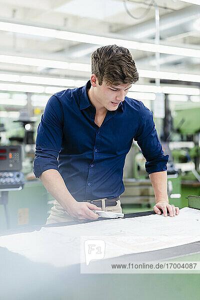 Junger Geschäftsmann mit Maschinenteil  der einen Grundriss auf einem Schreibtisch in der Industrie betrachtet