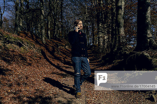 Mid adult man talking on mobile phone while walking in forest